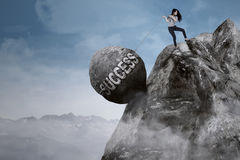 Businesswoman pulls success word on the mountain. Young businesswoman is pulling big rock with success word while climbing on the mountain Royalty Free Stock Photo