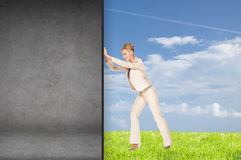 Businesswoman pushing away concrete wall Royalty Free Stock Image