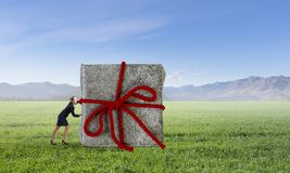 Get your gift. Mixed media. Businesswoman pushing big Christmas gift. Mixed media Stock Photos