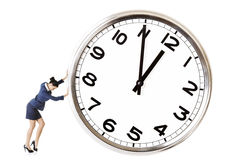 Businesswoman is pushing a big clock Royalty Free Stock Photos