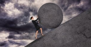Businesswoman pushing a 3D stone ball above her. Digital composite of Businesswoman pushing a 3D stone ball above her Royalty Free Stock Photo