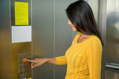 Businesswoman pushing elevator button Stock Images