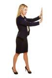 Businesswoman pushing imaginary object Royalty Free Stock Image