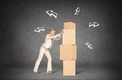 Businesswoman pushing tower of cardboard boxes Stock Photography