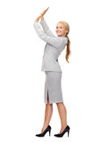 Businesswoman pushing up something imaginary Stock Images
