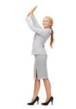 Businesswoman pushing up something imaginary Stock Images