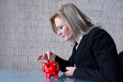 Businesswoman put coins into piggy bank Stock Images