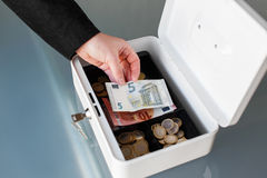 Businesswoman put five euro into safe box Stock Images
