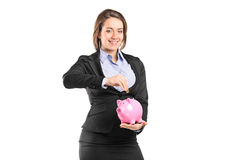 A businesswoman putting a coin into a piggy bank Royalty Free Stock Image