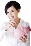 Businesswoman putting a coin into a piggy bank Royalty Free Stock Photo