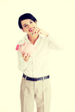 Businesswoman putting a coin into a piggy bank Royalty Free Stock Image