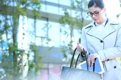Businesswoman putting digital tablet in purse outdoors Stock Image