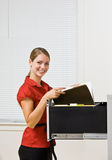Businesswoman putting file in file cabinet Stock Photo