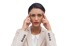 Businesswoman putting her fingers on her temples Stock Photo