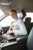 Businesswoman putting on her seat belt Royalty Free Stock Image