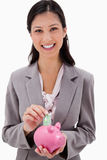 Businesswoman putting money into piggy bank Royalty Free Stock Image
