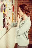 Businesswoman putting sticky notes on whiteboard. In office royalty free stock images