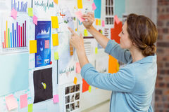Businesswoman putting sticky notes on whiteboard Stock Images