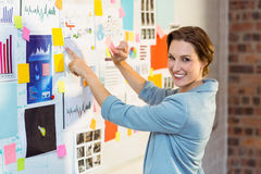 Businesswoman putting sticky notes on whiteboard Stock Photo