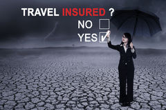 Businesswoman with question of travel insured. Image of Asian businesswoman using an umbrella while answering a yes option to a question of travel insured Royalty Free Stock Images