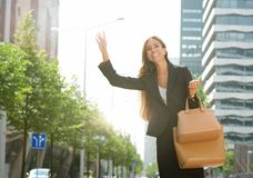 Businesswoman raising arm for taxi in the city Royalty Free Stock Photo