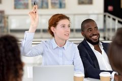 Businesswoman raising hand ask question at diverse group corporate training. Businesswoman raising hand ask question at diverse group corporate conference royalty free stock photo