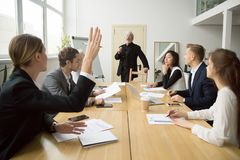 Businesswoman raising hand asking senior coach questions at team. Businesswoman raising hand up at diverse team meeting sitting at conference table, student Stock Photo