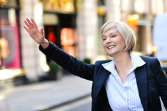 Businesswoman raising her arm to call a taxi. Middle aged business woman calling for taxi Royalty Free Stock Photos