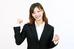 Businesswoman raising her arms in sign of victory. Young japanese businesswoman raising her arms in sign of victory Royalty Free Stock Images
