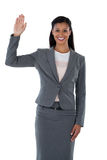 Businesswoman raising her hand. Against white background Royalty Free Stock Image