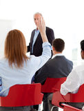 Businesswoman raising her hand up at a conference royalty free stock photo