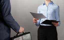 Businesswoman reaches out documents to a businessman with briefc Stock Images