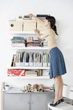 Businesswoman Reaching For Shelf In Home Office. Full length of young businesswoman reaching for shelf in home office Royalty Free Stock Photo