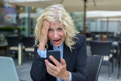 Businesswoman reacting in horror to her mobile Royalty Free Stock Photo