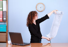Businesswoman reading blueprint Royalty Free Stock Image