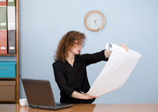 Businesswoman reading blueprint Stock Image