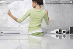 Businesswoman Reading Blueprint At Office Stock Image