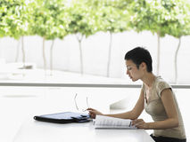 Businesswoman Reading Book At Desk Royalty Free Stock Photography