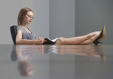 Businesswoman Reading Book With Feet On Conference Table Stock Photos