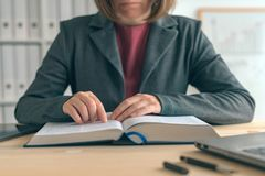 Businesswoman reading book at office desk royalty free stock images