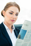 Businesswoman reading business newspaper Stock Photo