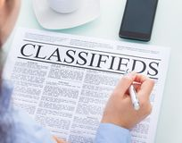 Businesswoman reading classifieds Stock Image