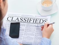 Businesswoman reading classifieds Royalty Free Stock Image