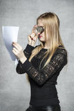 Businesswoman reading a contract with the magnifying glass Stock Photo