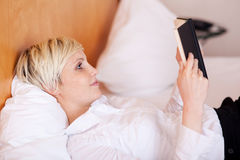 Businesswoman Reading Diary While Lying On Bed Stock Images