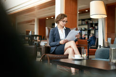 Businesswoman reading document at coffee shop Stock Photos