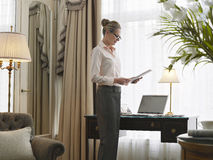 Businesswoman Reading Document In Home Office Stock Photos