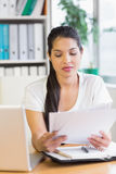 Businesswoman reading documents at desk Stock Photos