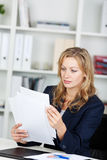 Businesswoman Reading Documents At Desk Stock Photography