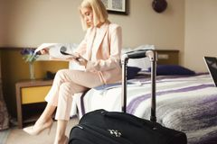 Businesswoman reading documents in hotel. Businesswoman reading documents. Female professional in hotel examining papers. Business lady go to business trip, copy Stock Images